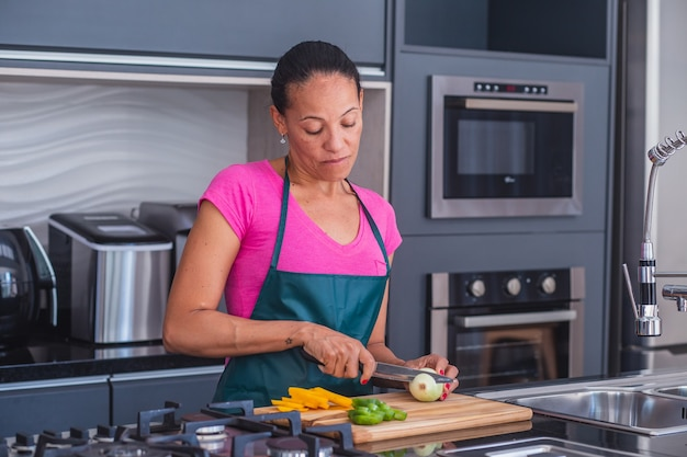 Woman using a knife and cutting onion.
