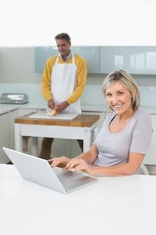 Женщина, используя ноутбук и человек, измельчение овощей