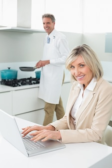 Женщина, используя ноутбук и человек, приготовление пищи