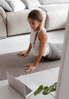 自宅でノートパソコンを使ってヨガをする女性