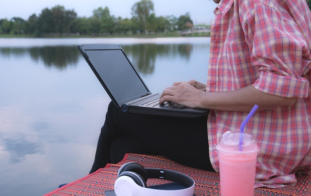 A woman using laptop computer while sitting beside river.