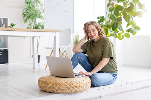 家のインテリアの床に座ってラップトップコンピューターを使用している女性。在宅勤務のフリーランスの女性