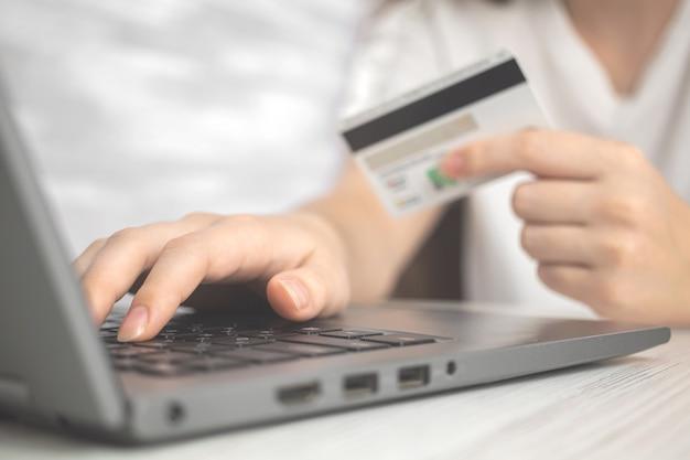 신용 카드를 손에 들고 노트북 컴퓨터를 사용하는 여자. 온라인 쇼핑, 돈과 전자 상거래의 개념. 인터넷 뱅킹 배경 사진
