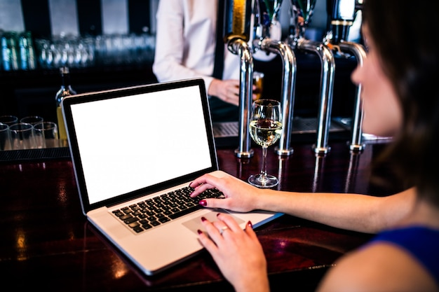 Woman using laptop and having a drink in a bar