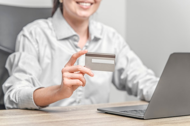 Woman using laptop and holding credit card in hands.