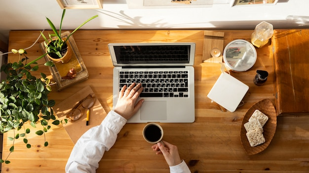 Woman using laptop and holding a cup of coffee