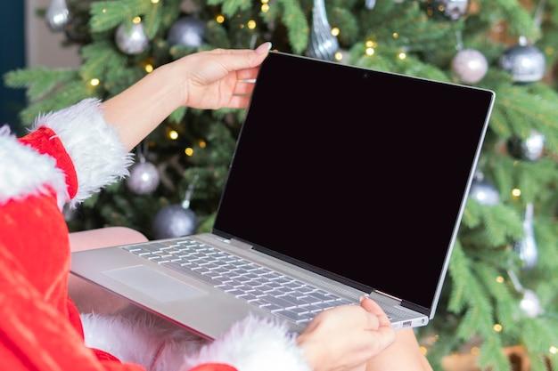 Женщина, используя ноутбук в комнате, украшенной на рождество. пустой экран для текста рекламы или дизайна