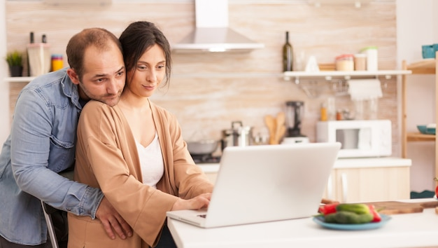 Woman using laptop in kitchen while her husband hugs her. happy loving cheerful romantic in love couple at home using modern wifi wireless internet technology