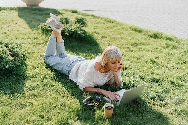 Женщина, использующая ноутбук, лежа на траве