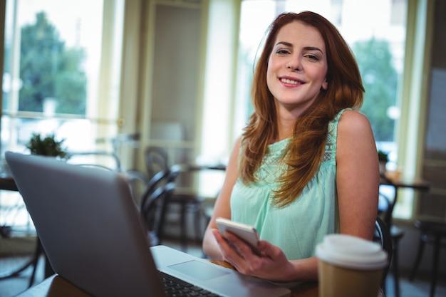 Donna con laptop e telefono cellulare in caffetteria ©
