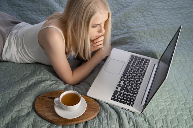 Женщина, использующая ноутбук на ее кровати.