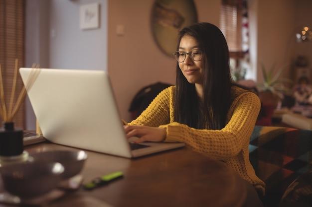 거실에있는 테이블에 노트북을 사용하는 여자
