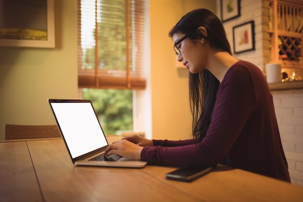 リビングルームのテーブルでノートパソコンを使用している女性