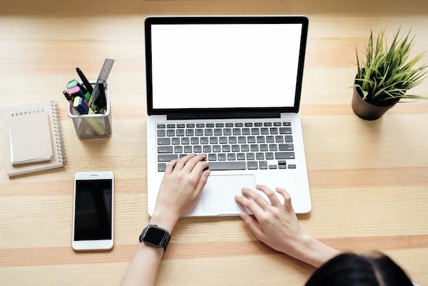 나무와 자연 배경으로 windows에 사무실 방에 테이블에 노트북을 사용하는 여자.