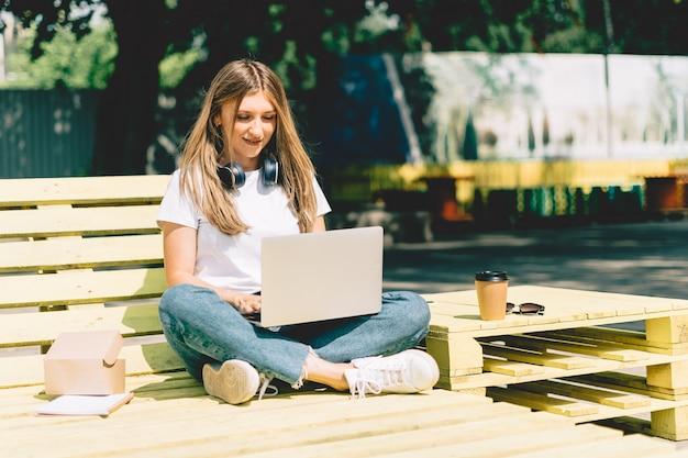Женщина, использующая ноутбук, сидя на скамейке