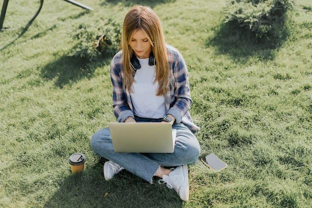 Женщина, использующая ноутбук, сидя на траве