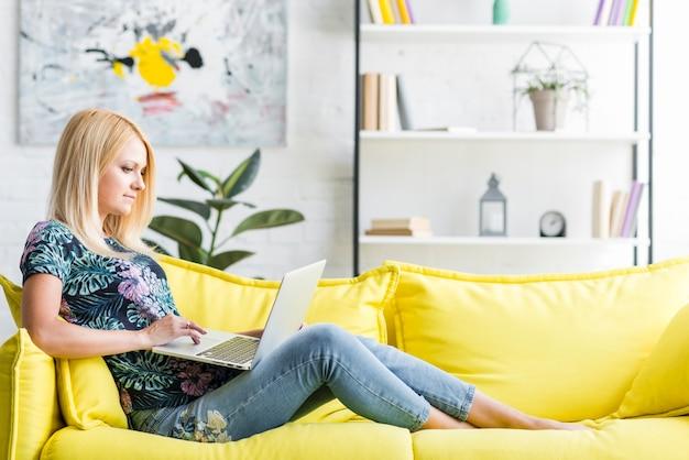 Woman using laptop sitting on sofa