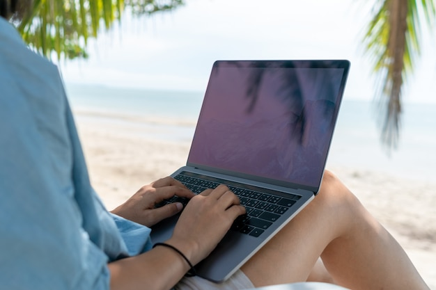 Woman using laptop and smartphone in vacation