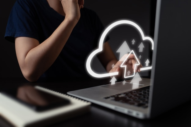 Woman using laptop for upload with cloud icon hologram effect