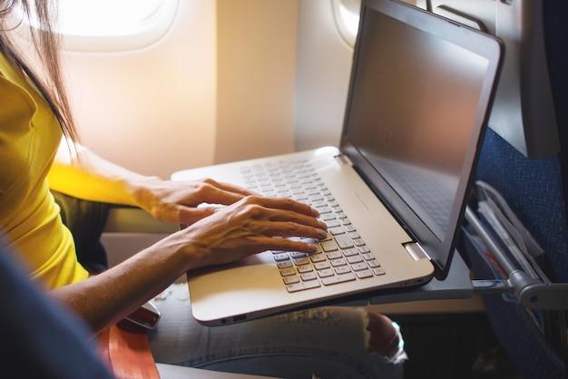 동안 노트북을 사용하는 여자는 창 근처 비행기에 앉아있다.