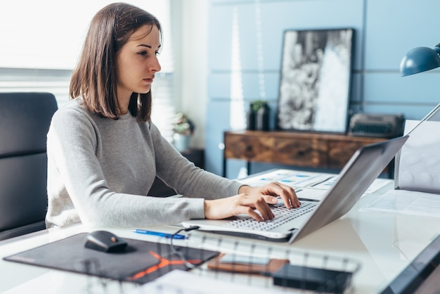 Woman using laptop while sitting at her desk. businesswoman in the office working on laptop.