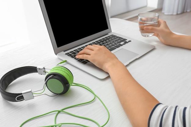 テーブルの上に接続されたヘッドフォンでラップトップを使用している女性