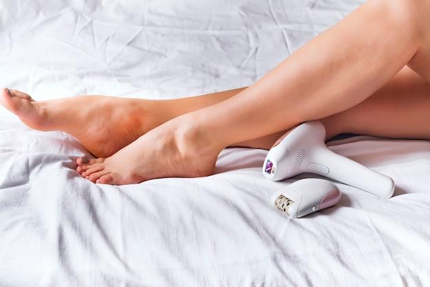 Женщина, использующая лазерный эпилятор или эпилятор для процедуры удаления волос у себя дома