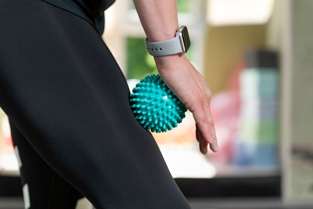 허벅지 근육에 근막 치료를 위해 마사지 도구를 사용하는 여자. 물리 치료용 롤러.