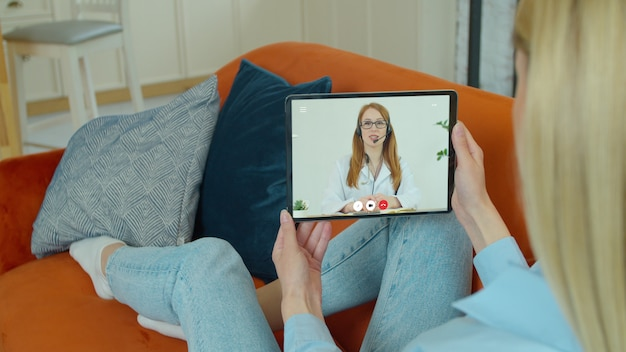Woman using medical app on digital tablet consulting with doctor via video conference