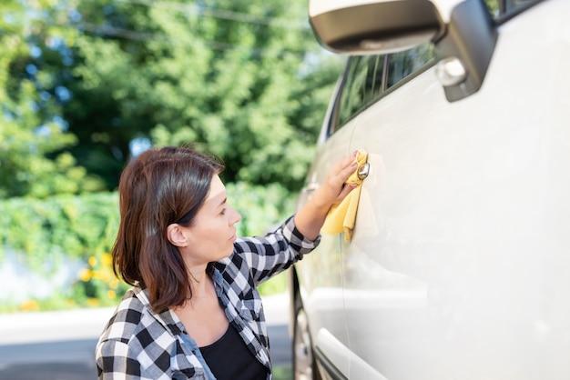 車の研磨にマイクロファイバーのぼろきれを使用している女性