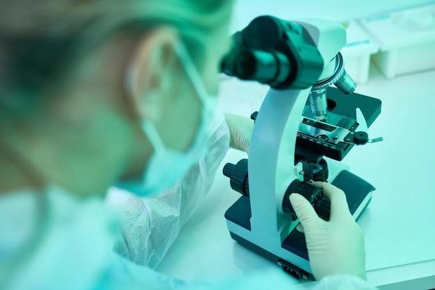 Женщина с помощью микроскопа в лаборатории