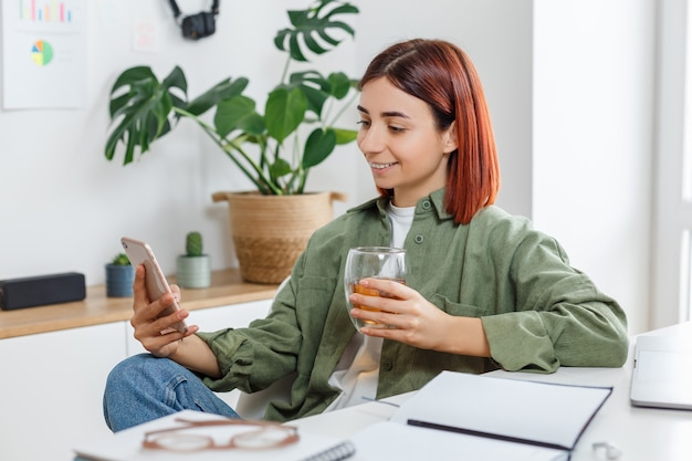 Женщина с помощью мобильного телефона и пить чай концепция онлайн-бизнеса или домашнего офиса связи