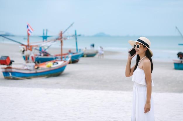 Woman using mobile phone on beach
