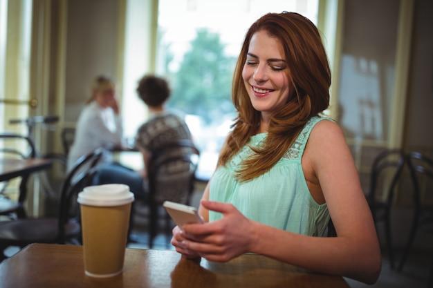 La donna con il cellulare in caffetteria ©
