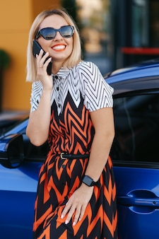 Donna che utilizza il telefono cellulare, la comunicazione o l'applicazione online, in piedi vicino all'auto sulla strada della città o sul parcheggio, all'aperto. car sharing, servizio di noleggio