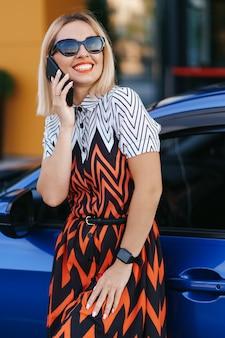 携帯電話、通信またはオンラインアプリケーションを使用して、都市通りや駐車場、屋外で車の近くに立っている女性。カーシェアリング、レンタルサービス