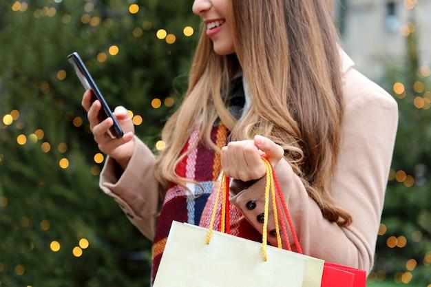 Женщина, использующая мобильный телефон для покупок в интернете и переноски сумок