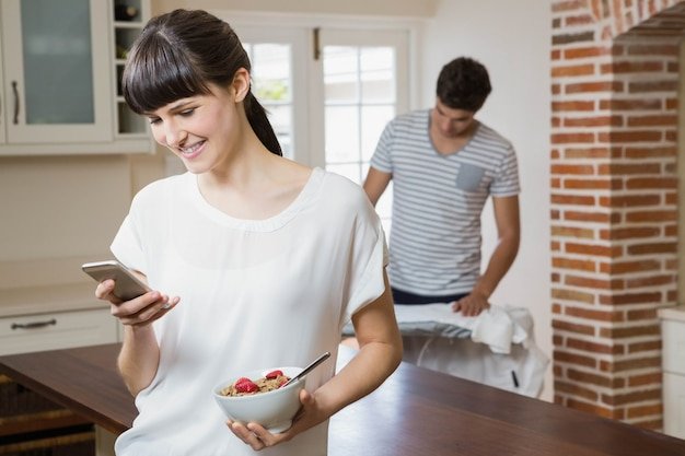 Woman using mobile phone and having breakfast cereals while man ironing a shirt
