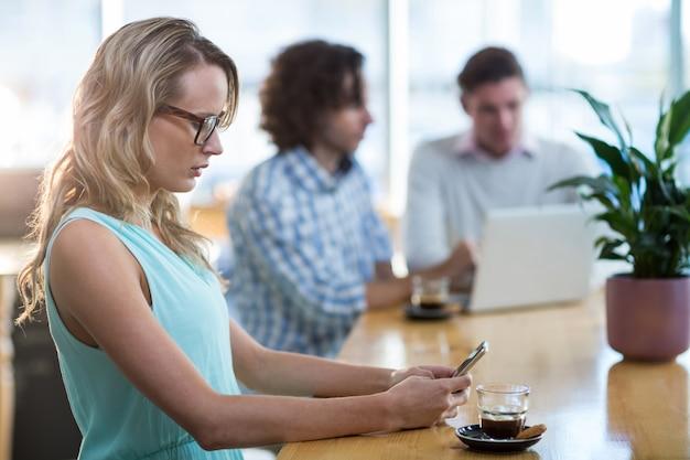カフェで携帯電話を使用している女性