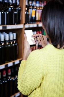 Женщина с помощью мобильного телефона в продуктовом разделе