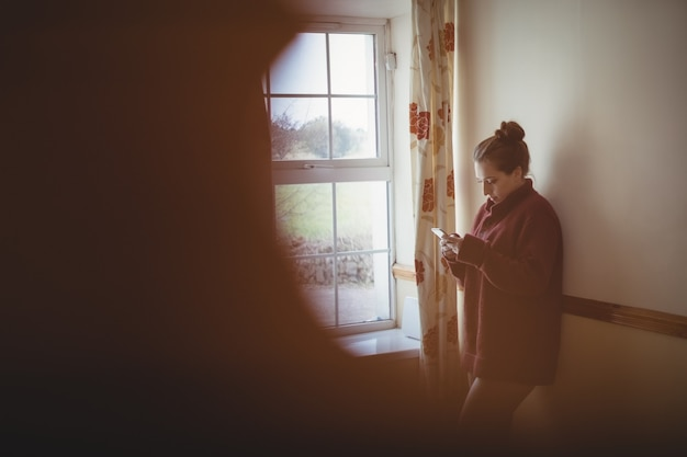 Woman using mobile phone near window at home