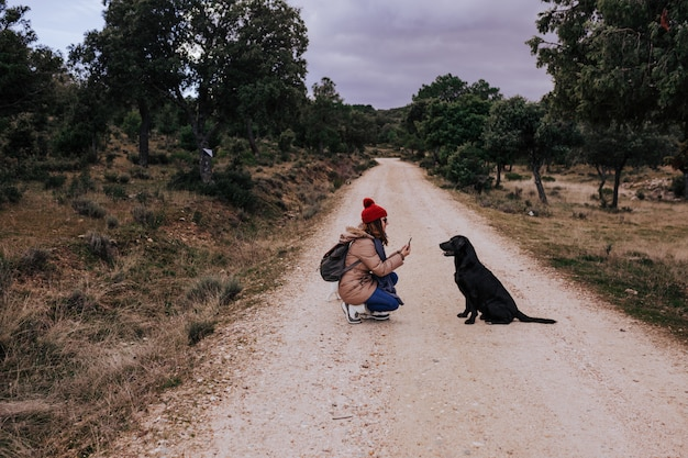 Woman using mobile phone outdoors in nature. beautiful black labrador besides.