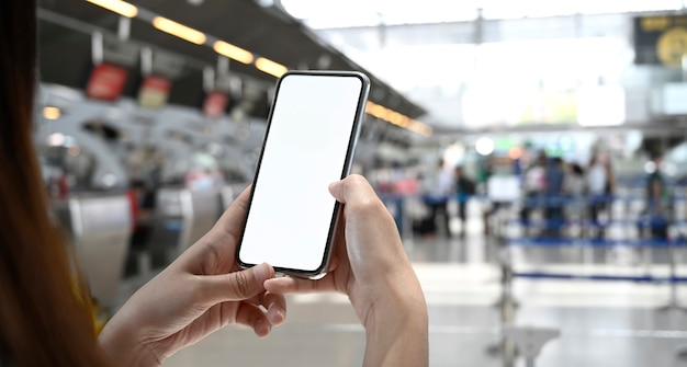Woman using mobile phone in terminal airport