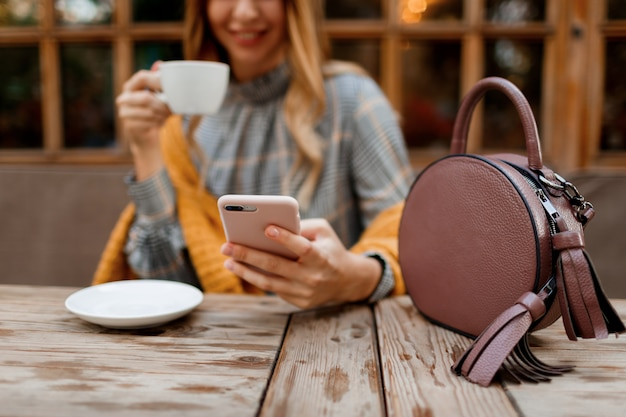 Woman using mobile phone, texting message and drinking coffee. stylish bag on table. wearing grey dress and orange plaid. enjoying cozy morning in cafe.