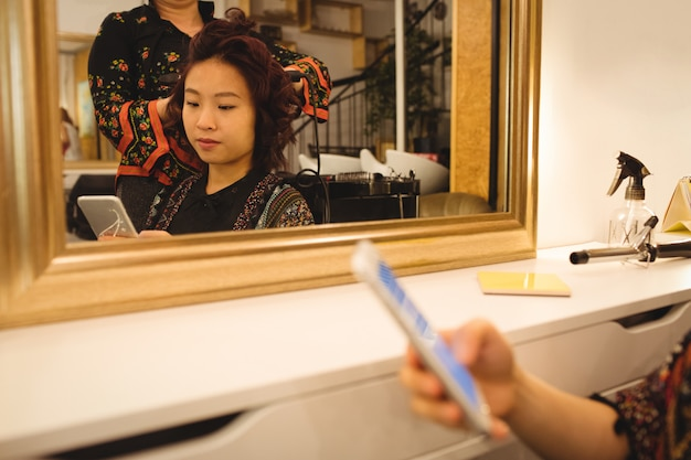 Woman using mobile phone while getting her hair straightened