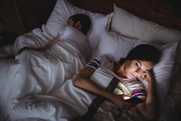여자가 침대에 누워있는 동안 휴대 전화를 사용 하여