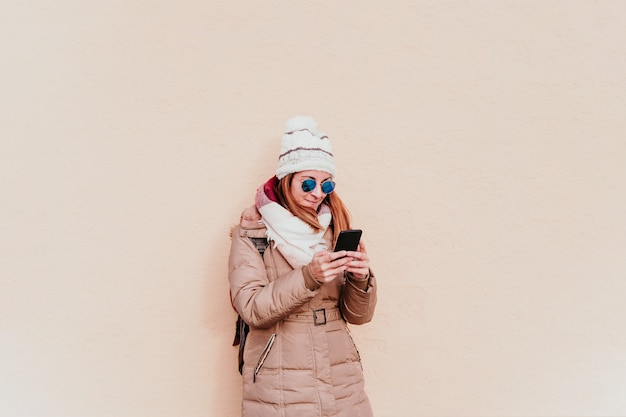 Woman using mobile phone on yellow wall. technology and winter concept