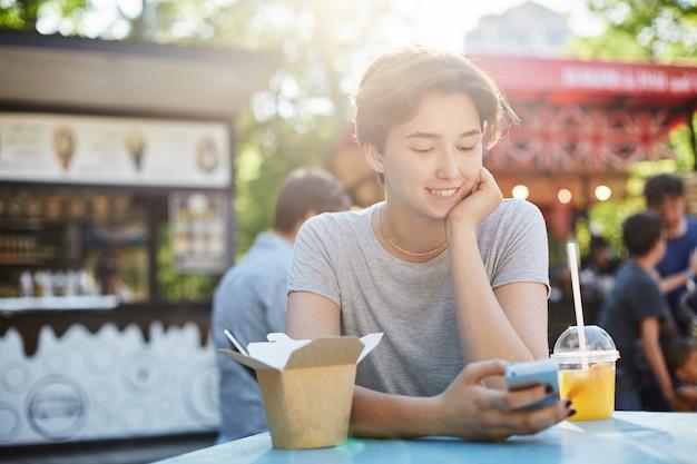 Donna che utilizza il telefono cellulare. giovane donna che scorre attraverso i social media alla ricerca di un nuovo lavoro