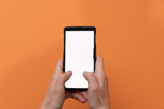 オレンジ色の背景に分離された携帯電話のスマートフォンを使用して女性。