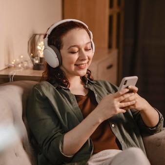 Женщина, использующая современные наушники и смартфон дома